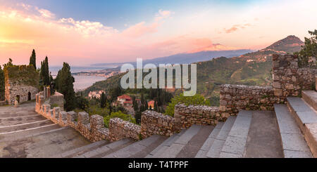 Panoramic view of smoking snow-capped Mount Etna volcano at sunrise, as seen from Taormina, Sicily - Stock Image