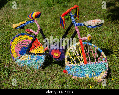 Bicycle, covered with colored knitted wool, seen in Eifel area near Daun, Germany - Stock Image