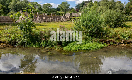 The River Coln flows through Bibury village's famous Arlington Row which is reflected in its calm waters - Stock Image