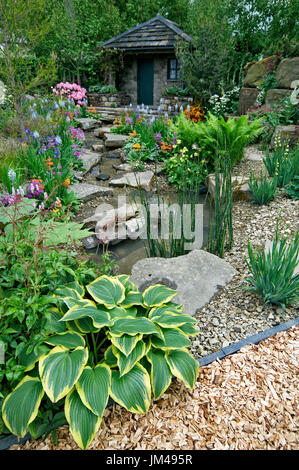 A country cottage garden in a wooded rockery with colourful planting - Stock Image