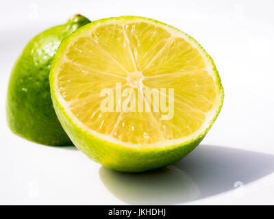 Two pieces of Lime cut in half - Stock Image