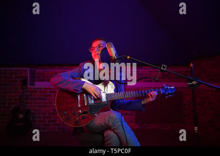 A young woman in glasses playing guitar and singing in neon lighting - Stock Image