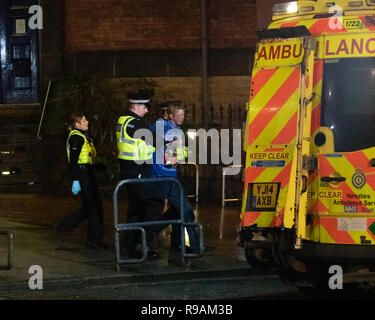Leeds, UK. 22 December 2018. A young man is helped into an ambulance in Leeds city centre during the early hours of saturday morning Credit: James Copeland/Alamy Live News - Stock Image