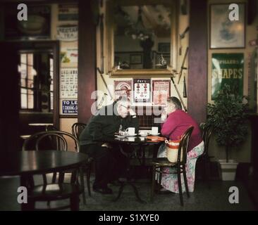 Couple having a cup of tea and a conversation in the Station Cafe, Bridlington, East Yorkshire, England, UK - Stock Image