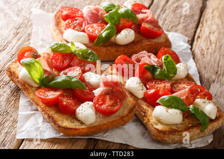 Italian open sandwiches with mozzarella, tomatoes, ham and basil closeup on the table. horizontal - Stock Image