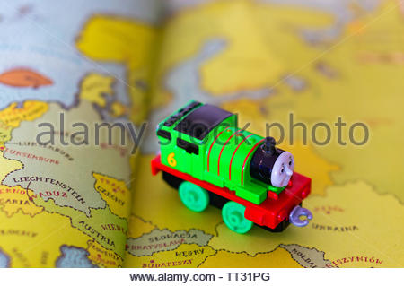 Green Peter Sam toy locomotive from the Thomas and Friends series on a page with map from a open atlas book on circa June 2019 in Poznan, Poland. - Stock Image