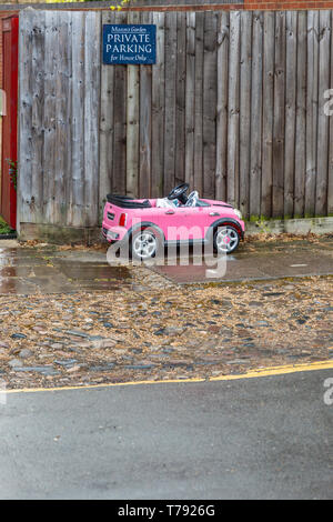 Humourous image of a small child's toy car parked below Private parking sign. Seen in Cambridge, England, UK. - Stock Image