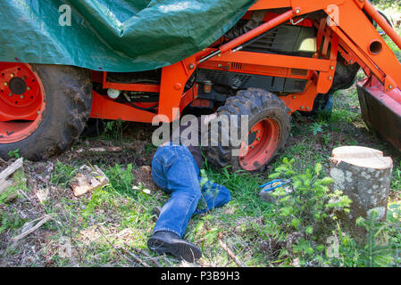 A mechanic laying on the ground underneath a tractor making repairs at a job site in the Adirondack Mountains, NY USA - Stock Image