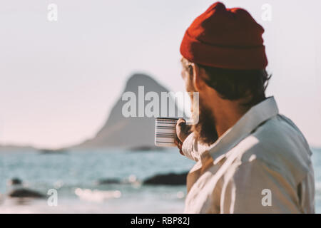 Summer vacations man traveling ocean beach guy holding tea cup lifestyle adventure outdoor - Stock Image