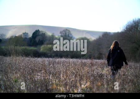 Woman walking in a field of weeds - Stock Image