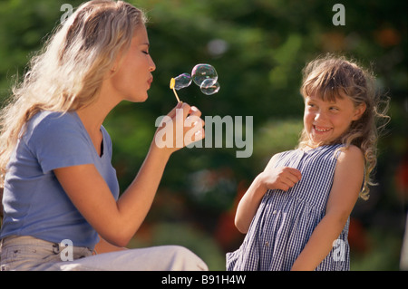 Mother and daughter blowing bubbles - Stock Image