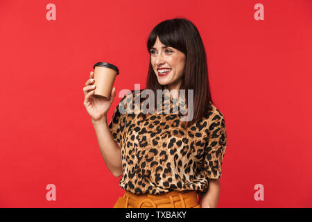 Image of a beautiful happy young woman dressed in animal printed shirt posing isolated over red background drinking coffee. - Stock Image