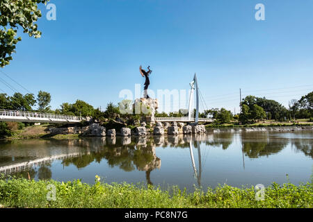 Keeper of the Plains, a steel sculpture by Blackbear Bosin, and a pedestrian suspension bridge. Wichita, Kansas, USA. - Stock Image