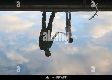 Reflection of father and daughter holding hands on a dock in the water amidst beautiful clouds - Stock Image