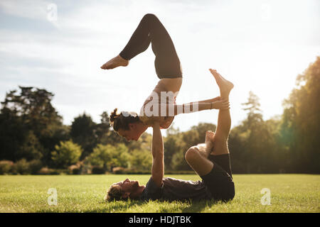 Fit young couple doing acroyoga on grass. Man and woman in park practising pair yoga poses in sunny morning. - Stock Image