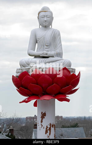 A statue of the Buddha on a lotus blossom outside the New York Buddhist Vihara Association in Queens Village, Queens, New York City. - Stock Image