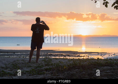 Silhouette of an adult male taking a picture of the sunset, Loyalty Beach, Seisia, Cape York Peninsula, Far North Queensland, FNQ, QLD, Australia - Stock Image