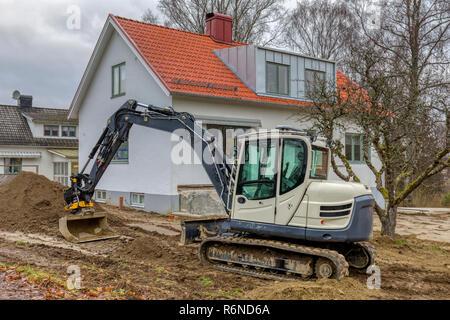 FLODA, SWEDEN - NOVEMBER 21 2018: Small excavator doing landscaping work in garden of detached house - Stock Image
