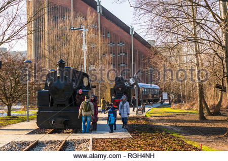 Poznan, Poland - January 19, 2019: People standing by a vintage exposition locomotive at the Rataje park. Church building in the background. - Stock Image