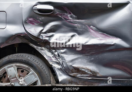 UK. Close up of a car door, badly damaged in a collision with another vehicle - Stock Image