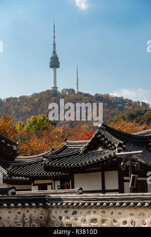 A view of Namsan Tower over the rooftops of houses at Namsangol Hanok Village, Seoul, South Korea on an autumn day. - Stock Image