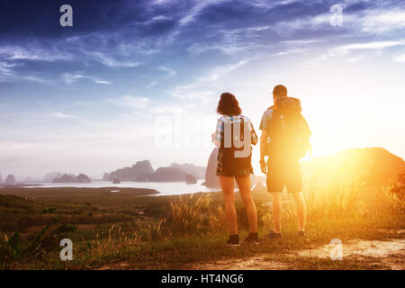 Two hikers backpackers view sunrise sunset - Stock Image