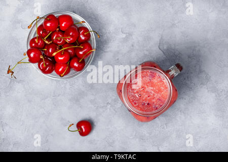 smoothies sweet cherry in a mason jar, fresh sweet cherry on a gray concrete background. view from above - Stock Image