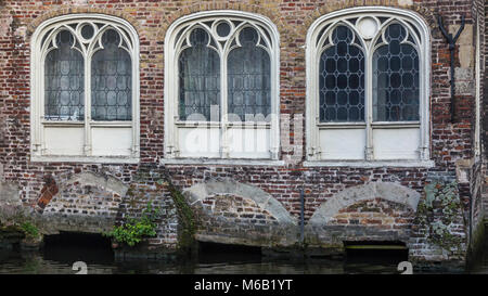 Three ornate stone carved arched windows on an ancient house on the magnificent canal waterway system in the heart - Stock Image