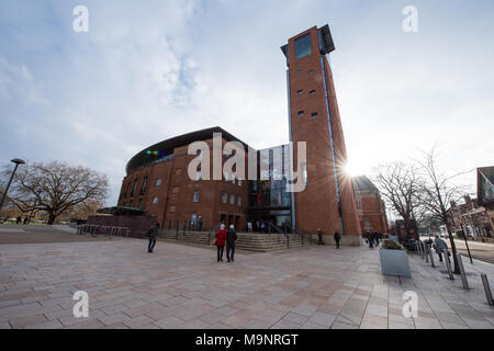 A burst of winter sunshine on the redbrick landmark tower at the Royal Shakespeare Theatre in Stratford-upon-Avon with a few people in the paved area - Stock Image