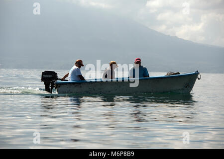 Indigenous, ethnic Maya men travelling by boat on Lake Atitlan. Lake Atitlán, Sololá Department, Guatemala. - Stock Image