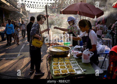 Thailand street food market scene with vendors serving customer and cooking  amidst the heat and smoke from a BBQ - Stock Image