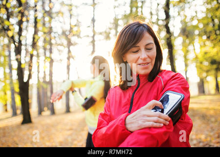 Two female runners with smartphone standing outdoors in forest in autumn nature, measuring time. - Stock Image