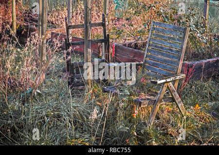 Abandoned garden furniture at an overgrown plot on Eglinton Growers allotment, Kilwinning, Ayrshire, Scotland - Stock Image