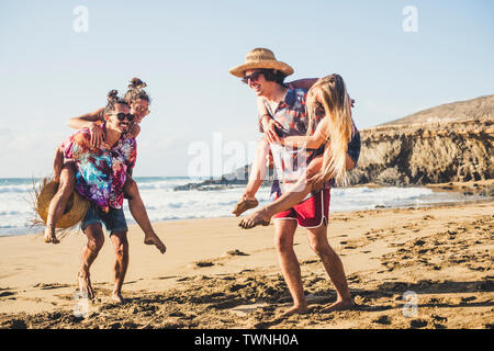 Happy young people have fun together - group of youth men and women enjoy the summer holiday vacation at the beach - men carry women on shoulder in su - Stock Image