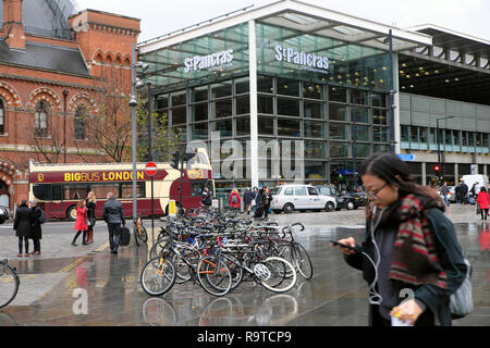 Woman looking at  her mobile phone outside busy city street with parked bikes and St Pancras Station building Kings Cross in London UK   KATHY DEWITT - Stock Image