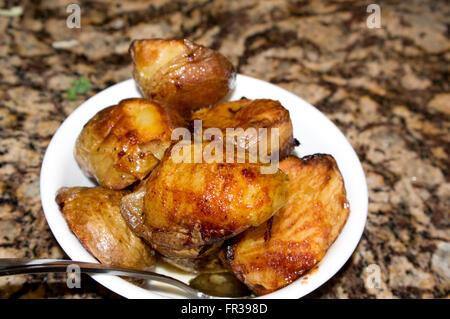 roasted potatoes, spoon,bowl - Stock Image