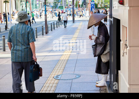 Side shot of a Shintoist monk asking for alms in the street in Fukuoka, Japan. - Stock Image