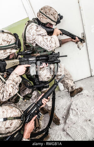 Marine assault team clearing rooms in an abandoned building. - Stock Image