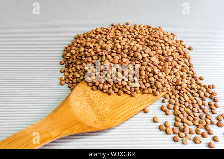 Pile of green lentils and wooden spoon isolated on white background - Stock Image