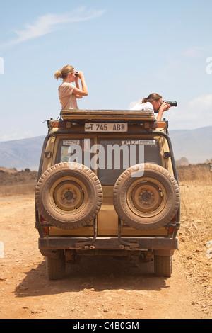 Tanzania, Ngorongoro. Two women look out from a safari vehicle at wildlife. - Stock Image