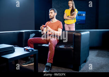 Young woman angry at her boyfriend playing video games with gaming console sitting on the couch at home or playing club - Stock Image