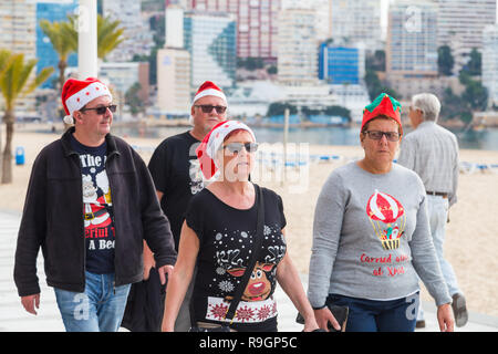 Benidorm, Costa Blanca, Spain, 25th December 2018. British tourists dress for the occasion on Christmas Day in this favourite getaway destination for Brits escaping the cold weather at home. Temperatures will be in the mid to high 20's Celsius today in this mediterranean hotspot.  Middle aged people wearing Christmas jumpers outside in the sun. - Stock Image