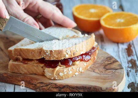 Womans hand cutting a peanut butter and Jelly sandwich on a rustic wooden cutting board. Selective focus on sandwich. - Stock Image