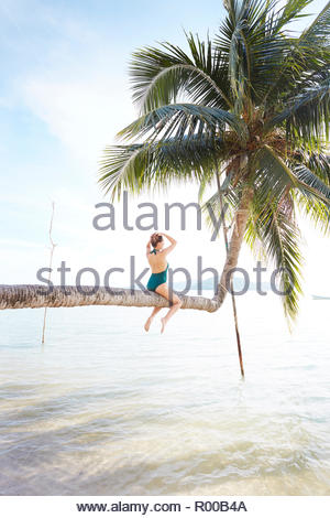 Young woman sitting on palm tree at beach - Stock Image