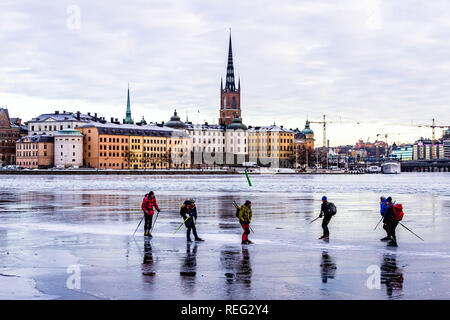 Ice skaters on frozen Lake Malaren, Stockholm, Sweden, with the island of Riddarholmen and the Riddarholm Church, the burial place of Swedish monarchs, behind them. 21st January, 2019. - Stock Image