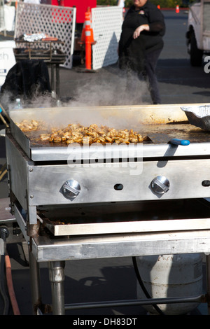 Grilled Chicken cooking outside on a gas grill at an outdoor event - Stock Image