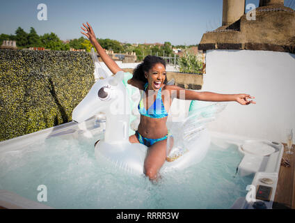 Playful, exuberant young woman in bikini sitting n inflatable pegasus in rooftop hot tub - Stock Image