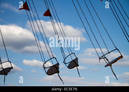 empty seats of a chairoplane in movement in front of blue sky with clouds - Stock Image