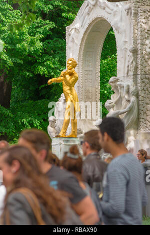 Vienna tourism, view of the golden Johann Strauss statue with a crowd of young tourists in the foreground, Stadtpark, Vienna, Wien, Austria. - Stock Image