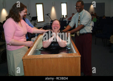 Woman reacts after being baptized at the Solid Rock Church in Riverdale Park, Maryland - Stock Image